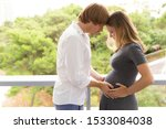 Young Pregnant Couple Posing O...