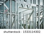 Steel House Frame Development. Caucasian Construction Contractor Wearing Safety Harness Working on the Frame. - stock photo