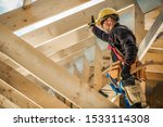 Construction Worker on Duty. Caucasian Contractor and the Wooden House Frame. Industrial Theme. - stock photo