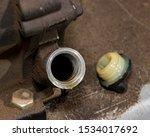 Closeup of small gas engine on lawn mower with oil fill plug removed showing oil level inside of motor. Concept of home dyi maintenance and repair