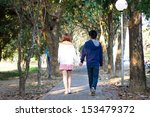 Small photo of Lover couple holding hands and walking together on the pathway