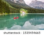 Famous Emerald Lake, Yoho National Park, British Columbia, Canada. Turquoise water and green trees. Red canoe on the lake.