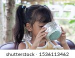 Small photo of Little girl is drinking water from a water dipper to quench thirst and refresh the body.