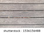 Small photo of natural greyed wood dock planks top view closeup, textured pattern background