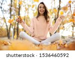 Cute smiling woman woman in autumn park with fall colorful background, sitting on blanket, throwing autumn fall leaves, enjoying warm sunny weather. Fall season concept. Outdoor lifestyle portrait. - stock photo