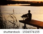 Stock photo silhouette of a man with a dog sitting on a pier near the lake at golden sunset 1536576155