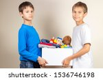 Small photo of Donation concept. Kids holding donate box with books, clothes and toys