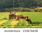 a agricultural tractor cuts a field of alfalfa with a side swather mower in southern Oregon