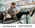Small photo of Young businessman sit alone and wait for flight. Hold phone in hands and cup of coffee. Flight pillow around neck. Expert or executive manager travel abroad. Waiting room