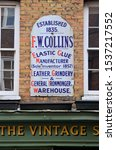 Small photo of LONDON - OCTOBER 6, 2019. An antique enamel sign daing from 1835 for an ironmonger over The Vintage Showroom, a clothes archive in Earlham Street, Covent Garden, London, UK.