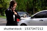 Small photo of Stressed female driver talking phone car collision scene, auto damage, insurance