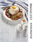 Small photo of Traditional loco moco of sticky rice, fried egg with a runny yolk, beef burger patty with brown mushroom gravy, cutlery, on a white wooden background, vertical view, copy space, close-up