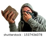 Small photo of young man as fanatic and aggressive anarchist rioter . furious and scary violent anti-system protester in face mask throwing brick looking hostile at fighting riot in radical demonstration