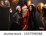 Small photo of Appealing blonde woman in red dress celebrating winter holidays with friends. Studio shot of girls dancing with balloons.