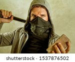 Small photo of young man as fanatic and aggressive ultra anarchist rioter . furious anti-system protester in face mask holding baton throwing brick looking hostile fighting at violent riot in radical demonstration
