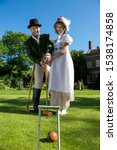 Small photo of Handsome man and beautiful woman dressed in vintage clothing on lawn in front of stately home, playing croquet with blue sky