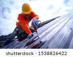 Roofer working on roof structure of building on construction site,Roofer using air or pneumatic nail gun and installing Metal Sheet on top new roof. - stock photo
