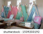 Small photo of Blue, green, pink and lama teepee's all set up for a sleepover birthday party. There is also fairy lights, bunting and face masks .