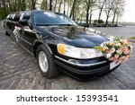 Black Wedding Limousine. Ornated with flowers. - stock photo