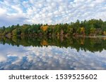 Autumn trees and clouds reflected in calm lake