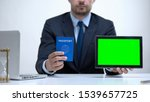 Small photo of Migration agent holding passport and tablet, tourist visa application online
