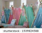Small photo of Pastel colored teepee's all set up for a girl's birthday party sleepover.
