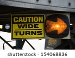 Small photo of 18-Wheeler Caution Wide Turns Sign with Lighted Arrow. Sign is on the undercarriage of a trailer on a big rig truck.