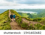 Small photo of A young couple holding hands while walking towards the Grota do Inferno viewpoint at Sete Cidades on Sao Miguel Island, Azores. The adults are walking away from the camera and looking at the lake view