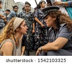 Small photo of BEIRUT, LEBANON - OCTOBER 26 2019: A protester faces off with a police officer during a sit-in on a main road in the Lebanese capital of Beirut, on the tenth day of anti-government demonstrations.