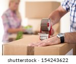 Close up of male hand packing cardboard box, concept moving house - stock photo