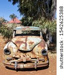 Small photo of Derelict abandon old car, full of rust with a lot of damage, used as a barrier to close off walk areas.