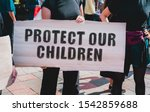 Stock photo the phrase protect our children drawn on a carton banner in hand a girl holds a cardboard with 1542859688