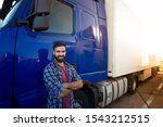 Professional truck driver with crossed arms standing by his semi truck. Trucker occupation and transportation services. - stock photo