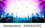 Small photo of Concert hall crowded with people in front of a stage lit for the gig