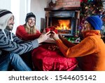 People in warm clothes sitting by the fireplace and cheering with egg punc drink, celebrate Christmas and New Year.Cheerful friends in winter clothes drinking hot wine to warm up
