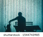 Stock photo silhouette on turquoise office curtain of a sitting man caressing his labrador dog s nose 1544743985