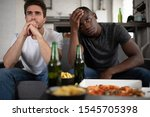 Small photo of Displeased multicultural men in casual outfit clasping hands and touching forehead while sitting on sofa near table with snacks and beer and watching lame match of favorite team