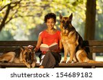 Stock photo photo of woman sitting on a bench with two german shepherds 154689182
