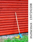 Small photo of Toy shovel and spate standing next to red wooden wall.