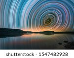 Beautiful night landscape with small lake and mountains. The colorful star trails on the sky. Night time lapse photography.