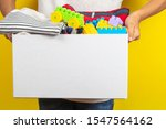Small photo of Donation concept. Kid hands holding donate box with books, clothes and toys ober yellow background