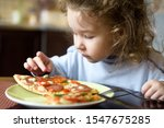 Child Looks At Pizza On Table....