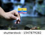 Small photo of Poor Ecuador in the hands of powerful people. Young man holds flag of Ecuador near stream. Concept of humanity and dominance. Prove of depraved and avariciousness. Colour man waves with flag.