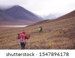 A scenery of people walking in the beautiful Gates of the Arctic National Park