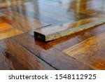Small photo of A piece of parquet floor tile slab sticking out after being stepped on as the wooden strip has become unglued and loose due to wear and tear over time.