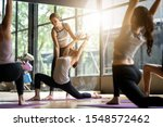 Small photo of Group of multi ethnics people learning Yoga class in fitness club. Female Caucasian instructor coaching and adjust correct pose to Asian girl student at front while others doing follow them.