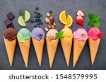 Small photo of ice cream flavor in cones blueberry ,lime ,pistachio ,almond ,orange ,chocolate ,vanilla and coffee set up on dark stone background . Summer and Sweet menu concept.