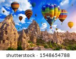 Small photo of Colorful hot air balloon flying over Cappadocia, Turkey.