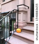Small photo of Carved Halloween Pumpkin sitting on New York Stoop