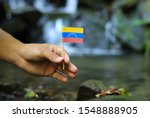 Small photo of Poor Venezuela in the hands of powerful people. Crooked man holds flag of Venezuela near stream. Concept of dominance and criminality. Prove of depraved and avariciousness. Problems with drogs